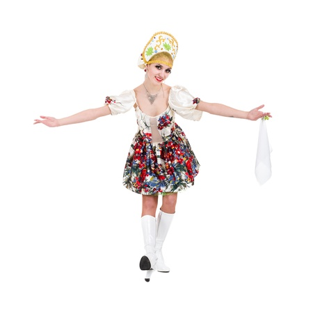 Attractive woman wearing a folk russian dress dancing against isolated white background photo