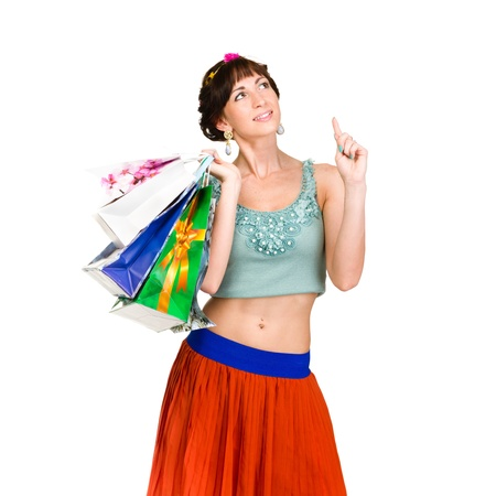 Pensive shopping woman holding bags and smiling isolated on white background. photo
