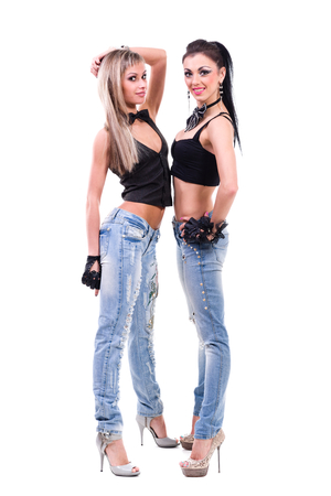 foreplay: two sexy girls in jeans isolated on white background in full length. Stock Photo