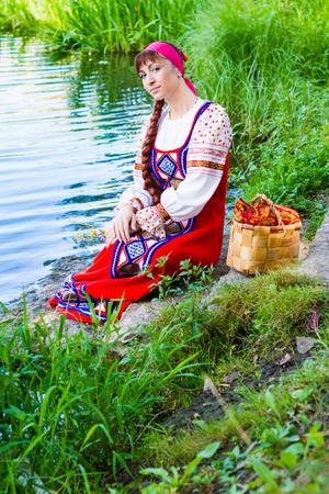 Vrouw in rokkostuum gestileerde Oekraïense folk poseren op de rivier