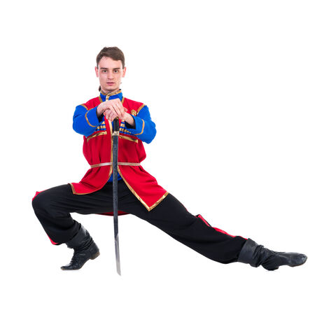 Russian cossack dance. Young dancer in ethnic clothes  posing with sword,  full length portrait isolated over white background