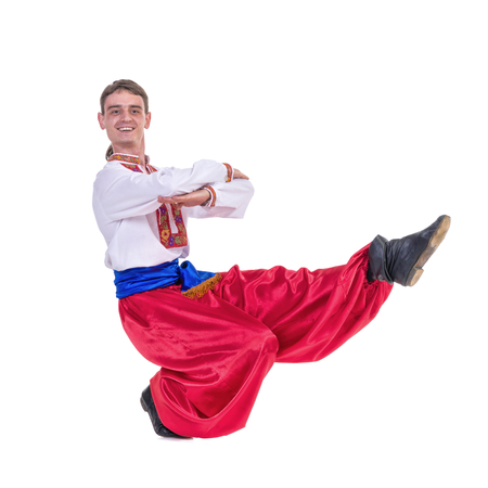 Russian cossack dance. Young dancer in ethnic clothes dancing,  full length portrait isolated over white background photo