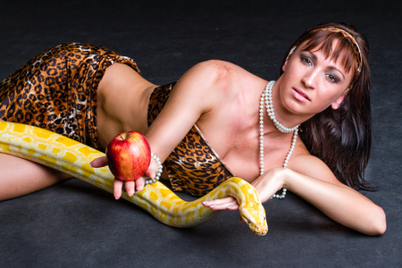 Woman with a snake eating red apple on black photo