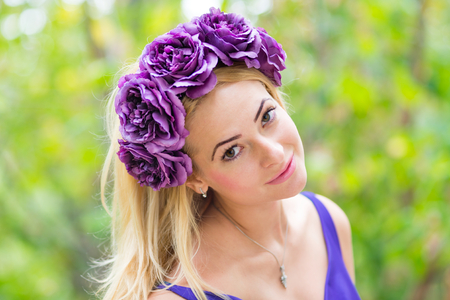 Beauty portrait of young pretty woman with flower wreath in her hair photo