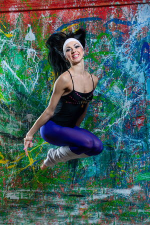 Portrait of a young lady, jumping in front of art graffiti photo