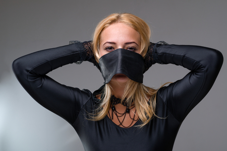 silenced: girl with self-adhesive tape over her mouth on gray Stock Photo