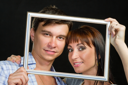 making faces: Young couple having fun making faces through tablet frame Stock Photo