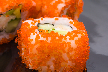 prepared food: Sushi roll close up on a black