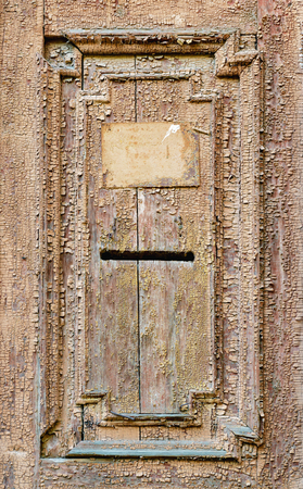 Vintage mail slot in a wooden door with patterns