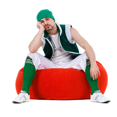 melancholy: Melancholy man dressed like a gnome sitting on red bag with gifts. Isolated over white background in full length.