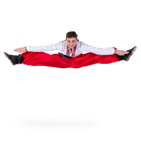 Russian cossack dance. Young dancer in ethnic clothes jumping,  full length portrait isolated over white background Stock Photo