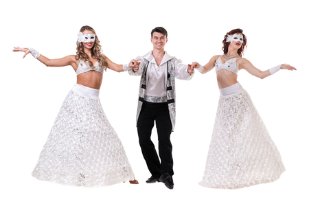 uplift: Three carnival dancers wearing a mask dancing, isolated on white background in full length. Stock Photo