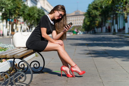 young businesswoman with phone sitting on the bench