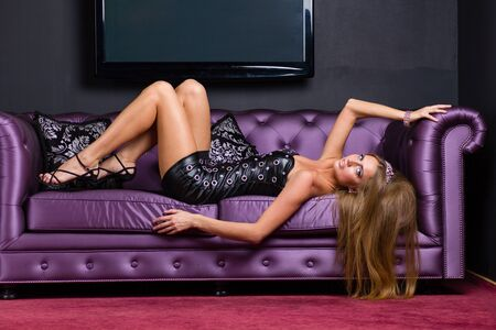 alluring: alluring woman wearing a short dress relaxing on a sofa