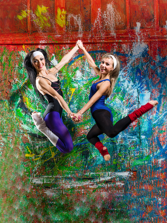 outdoor exercise: Portrait of two fit young women jumping in front of bright colored wall