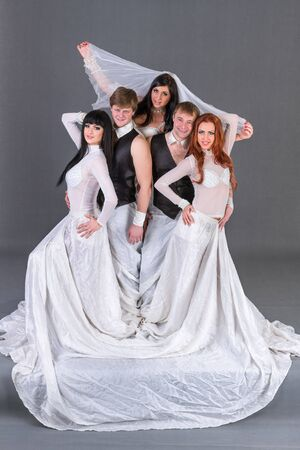 melancholia: Actors in the wedding dress dancing. On a gray background in full length. Stock Photo