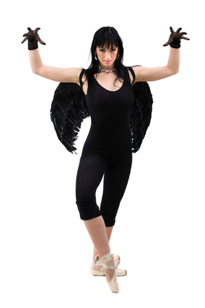 dark angel: young woman dressed as dark angel dancing, isolated in full body on white background