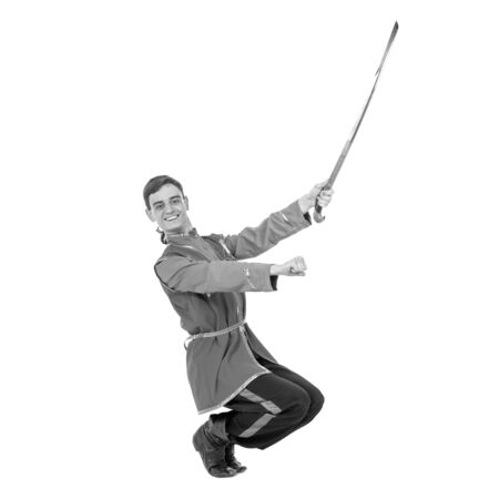cossack: colorless full length portrait of Russian cossack dance. Young dancer in ethnic clothes posing with sword, isolated over white background