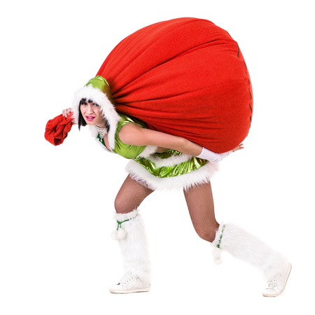 Woman dressed like a funny gnome pulls red bag with gifts. Isolated on white background in full length. Stock Photo