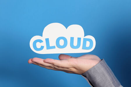 technology symbols metaphors: Womans hand holding a paper cloud with word Cloud. Cloud computing concept.