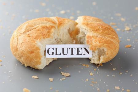celiac disease: Piece of paper with the word gluten in a bun. Celiac Disease concept.