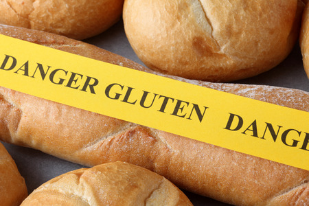 celiac: Yellow paper with the words Danger gluten on a buns. Celiac Disease concept. Stock Photo