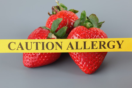 Strawberry allergy concept. Yellow paper with the words