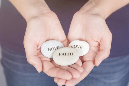"""geloof hoop liefde: Drie stenen met de woorden """"Faith"""", """"Hoop"""", """"Love"""" in de palmen van de vrouw. Stockfoto"""