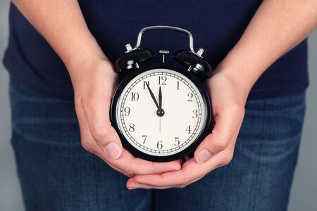 Womans hands holding and showing alarm clock. Five minutes before deadline. Stock Photo