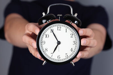 seven o'clock: Its almost seven oclock!. Womans hands holding and showing alarm clock. Stock Photo