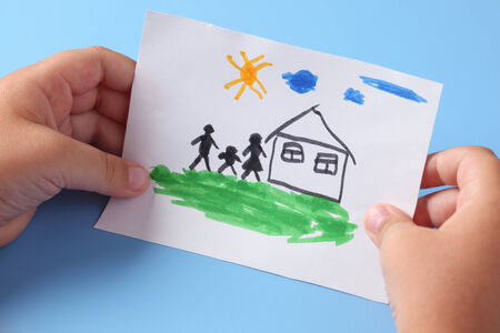 father and son holding hands: Child holds a drawn house with family. Stock Photo