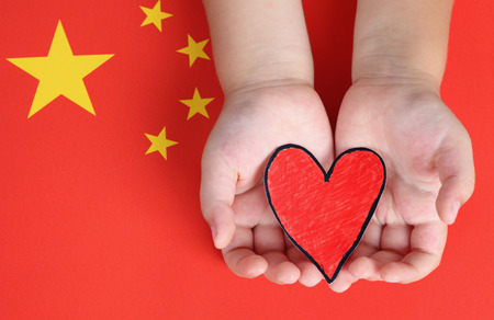 child's: Childs hands hold red paper heart against Chinese flag.
