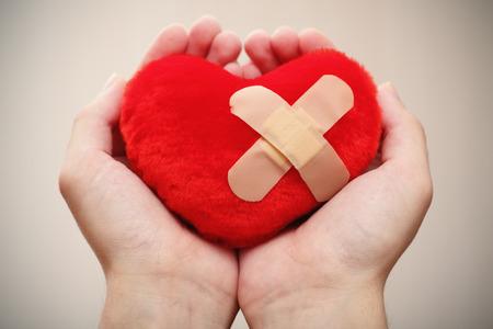 手のひらで絆創膏クロスに赤いハート型です。 写真素材