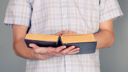 holding bible: Young man holding and reading old book.
