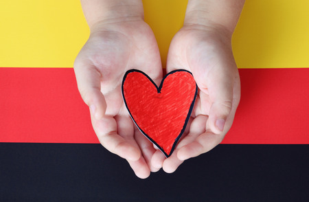 pledge: Childs hands hold red paper heart against German flag. Stock Photo