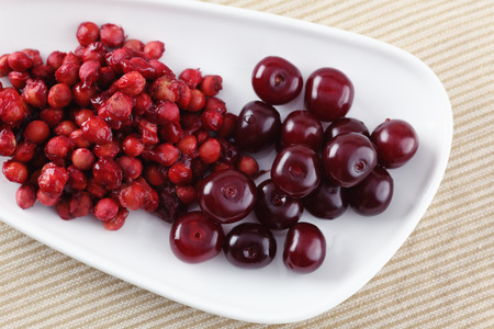 pits: Cherries and cherry stones (pits) on a plate.