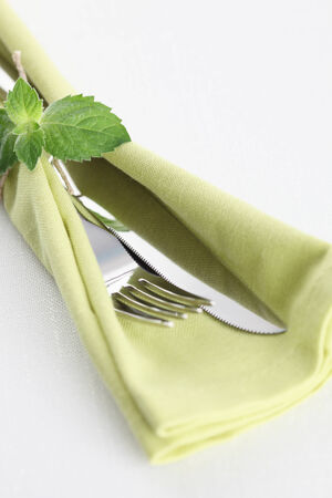 mint leaves: Fork, knife on green napkin with mint leaves Stock Photo
