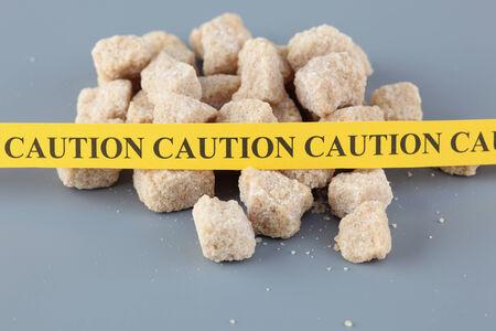 caution tape: Dangers of Sugar concept. Sugar free concept. Sugar heap with caution tape. Stock Photo