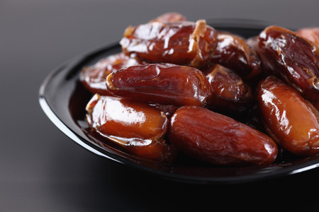 Date fruit in a black plate.