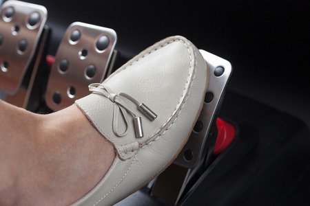 Woman's foot pressing the gas pedal. Stock Photo