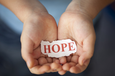 hope: Torn piece of paper with the word Hope in the childs palms. Stock Photo