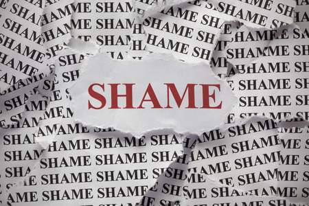 shame: Torn pieces of paper with words Shame