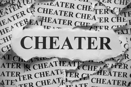 cheater: Torn pieces of paper with the word Cheater. Black and White. Close-up.