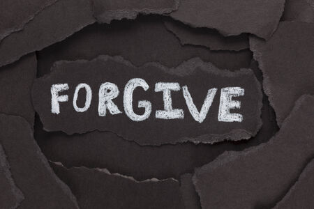 forgive: Forgive. Torn pieces of black paper and the word Forgive. Close-up. Stock Photo
