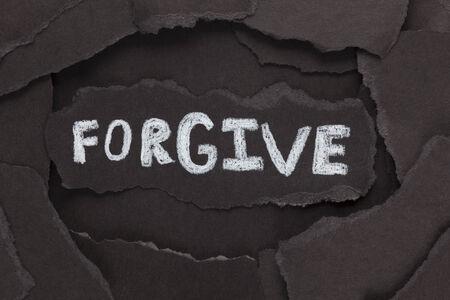 """to forgive: Perdona. Los trozos de papel negro y la palabra """"Perd�name"""". De cerca."""