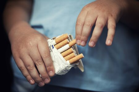 cigarette pack: Child takes out cigarette from pack of cigarettes.