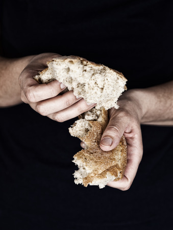 Woman\'s hands holding a pieces of bread. A helping hand concept  Standard-Bild