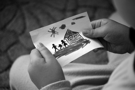Child holds a drawn house with family. Black and White.