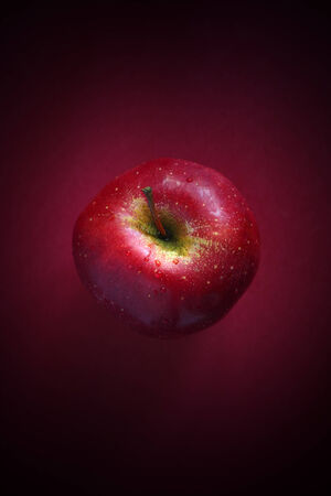 Red apple on red background. photo