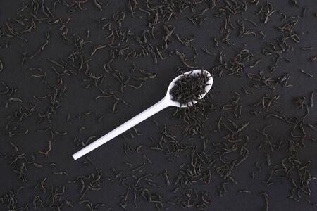 plastic spoon: Black tea in a plastic spoon on black background. Stock Photo